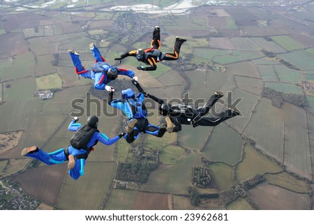 Five skydivers performing formations