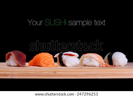 Five species of fish sushi on bamboo board, text space