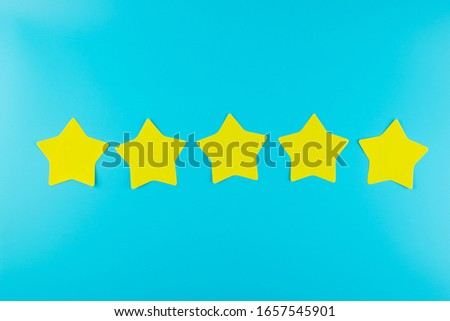 five star yellow paper note on blue background with copy space for text. Customer reviews, feedback, rating, ranking and service concept.