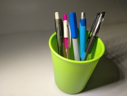 five stationery seen in a light green plastic cup, on a white paper background illuminated by light