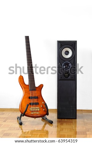 Five string electric bass guitar on a stand next to a floor-standing loudspeaker - stock photo