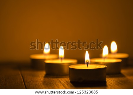 five tea lights on a table, shallow depth of field