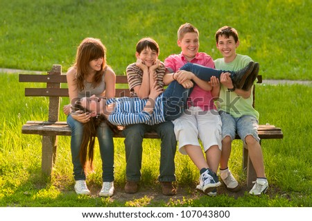 Five teenage boys and girls having fun in the park on sunny spring day.