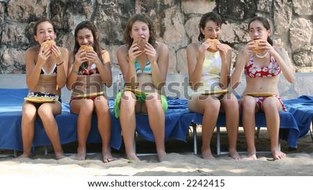 Five teenage girls eating hamburgers on the beach