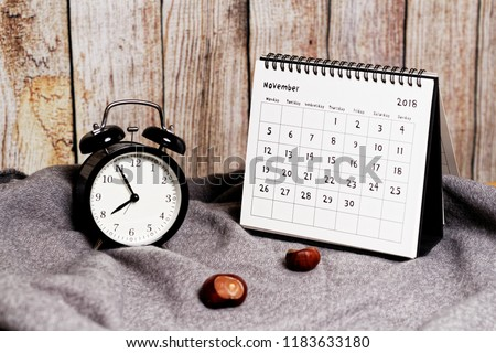 Five to eight on vintage clock, chestnuts and November 2018 calendar. Autumn time and mood