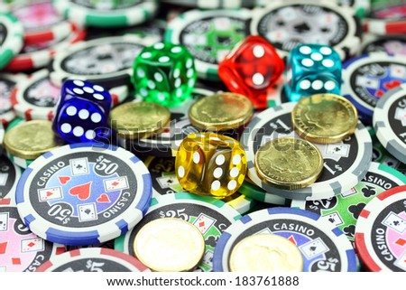 Five translucent colored dice laying on a pile of gambling chips of various denominations, with some gold coins also lying on the gambling chips