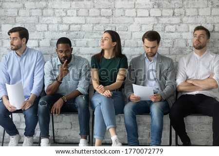 Five unemployed multi racial people wait turn feels nervous due job interview. Girl and guys looking pensive and anxious worried about upcoming meeting with HR manager. Concept of competition, hiring