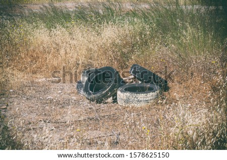 Five used car tires dumped in the grass in an abandoned area in the resort area (Rhodes, Greece)