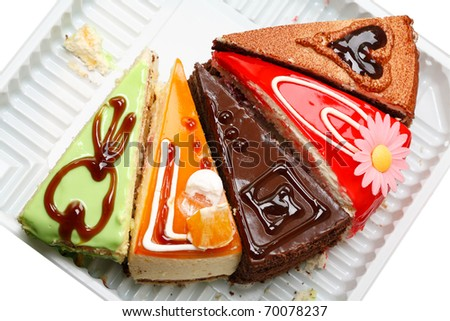 Five various pieces of cake on a plastic tray - stock photo