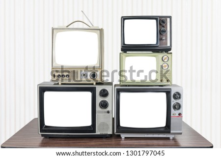 Five vintage televisions on old wood table with cut out screens. #1301797045
