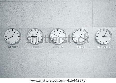 five wall clocks showing time in different capitals of the world