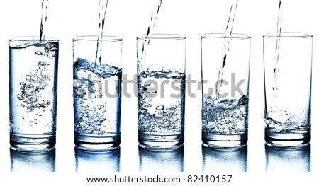five water glasses being filled in descending order - stock photo