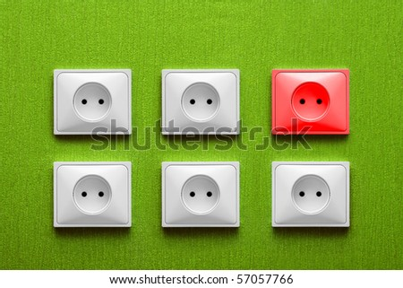 Five white and one red electric sockets in a green wall