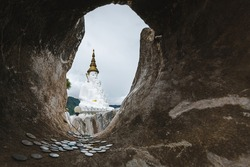 Five white Buddha statue is one famous landmark with a rock frame and Baht coins inside the hole rock at Wat Phra That Pha Sorn Kaew, Khao Kho District, Phetchabun, Thailand