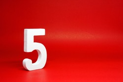 Five ( 5 ) white wooden  Isolated Red Background with Copy Space - New promotion 5% Percentage  Business finance Concept