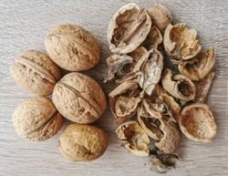 Five whole walnuts and nutshell on a wooden table