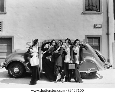 Five women standing in front of a car