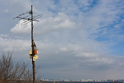 Five wooden nesting houses  for wild birds are attached to the antenna pole high above the city, on a hill. Background is blue spring sky with white clouds. Taking care of ecology and nature. Sunlight