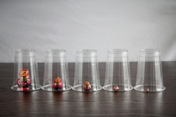 Five wooden Russian Matryoshka (Babushka) dolls individually isolated inside clear disposable plastic cups
