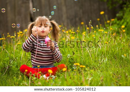 Five-year girl blowing soap bubbles in the park