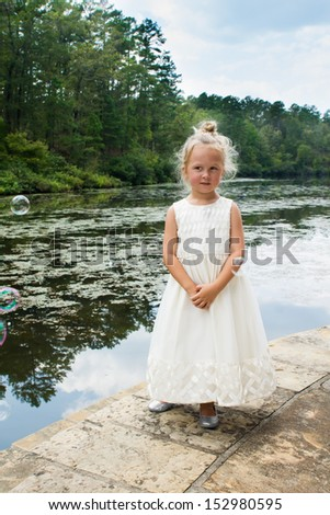 Five-year girl in a beautiful white dress standing near a pond overgrown with duckweed