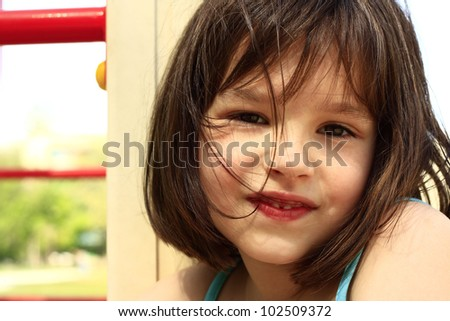 Five-year girl smiling on the background of children's playground summer day