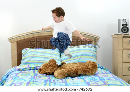 Five year old boy in pajamas jumping in bed stock photo for 5 yr old beds