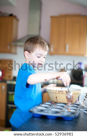 five year old boy making chocolate cakes