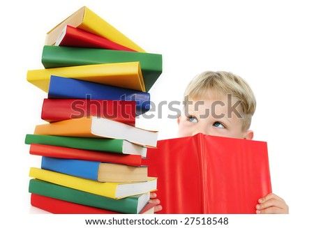Five year old boy reading a book, with a stack of books next to him. Isolated on white.