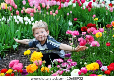 Five year old boy surrounded by colorful spring flowers