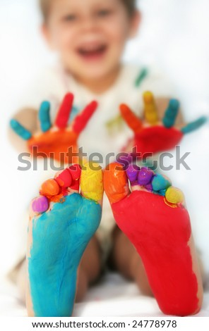 Five year old boy with feet and hands painted. Shallow DOF with focus on feet.