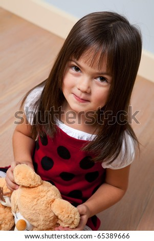 Five year old cute girl holding soft toy indoors