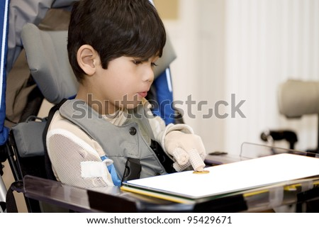 Five year old disabled boy studying in wheelchair, pointing at object on book