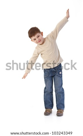 Five year old little boy imitating flying as an airplane, smiling.