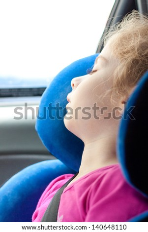 Five years old blond caucasian child girl sleeping while traveling in a car seat