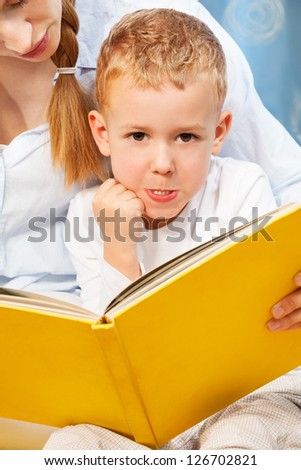 Five years old boy bored and prank with face expression while his mother trying to teach him to read