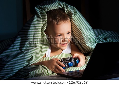five years old happy kid hiding under blanket playing computer games