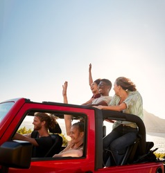 Five young adult friends on a road trip driving in an open top jeep by the sea