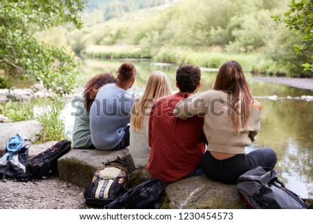 Five young adult friends taking a break sitting on rocks by a stream during a hike, back view, close up