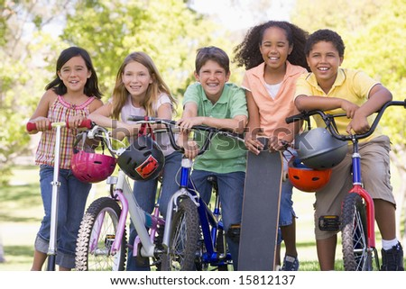 Five young friends with bicycles scooters and skateboard outdoors smiling - stock photo