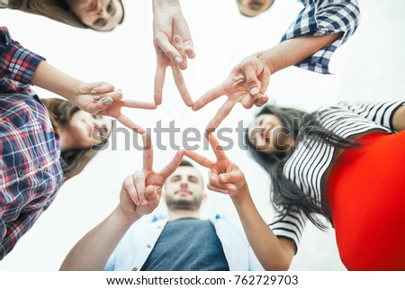 Five young smiling women and men make star shape from fingers. Happy friends or students show a sign with their hands - a symbol of success, victory, unity, team #762729703