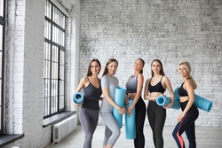 Five young women smiling at health club. Sporty attractive people practicing yoga, working out.
