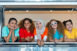 Five young working women from different ethnic groups or races standing next to each other at the cabin car window. Friendship across cultures during vacation