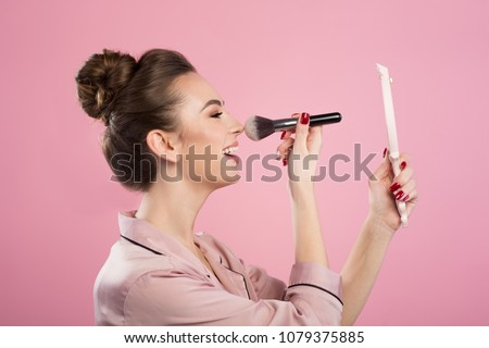 Fix makeup. Profile of cheerful young female is standing with hand mirror and powdering her nose using professional brush. Isolated on pink background