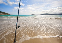 Fixed fishing rod set up on a beach near the surf on the incoming tide.  Blue sky with clouds, turquoise sea.