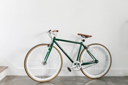 Fixed Green and Brown Bicycle in Modern Home, Fixie Bike inside hous​e, white wall background, isolated retro bicycle