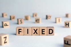 Fixed - word from wooden blocks with letters, fixed interest rates or costs  concept, random letters around, top view on wooden background