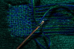 Fixing a hole in a green sofa by darning it.