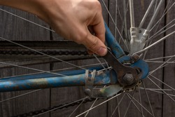 fixing an old rusty bike with a wrench; turns the nuts with a wrench on the wheel of an old bike