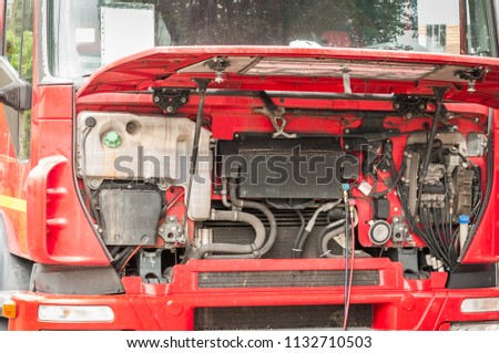 Fixing and repairing big heavy red semi truck with open hood on the street as regular maintenance service, close up